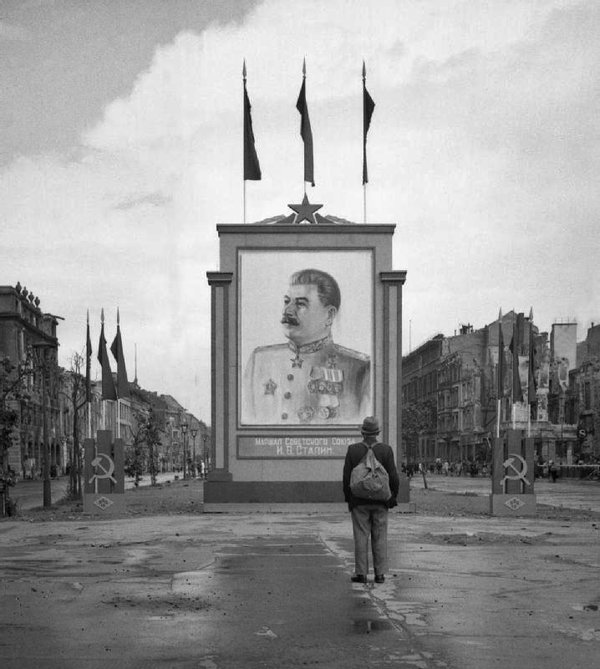 A-German-civilian-looks-at-a-newly-placed-poster-of-Stalin-on-the-Unter-den-Linden-in-Berlin-1945.